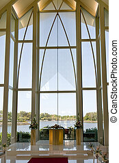 Modern wedding chapel with view through glass windows at...