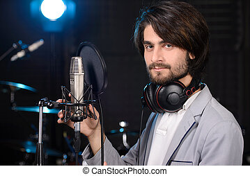 Recording Studio - Portrait of young man recording a song in...