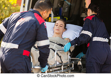 paramedics taking patient into an ambulance - paramedics...
