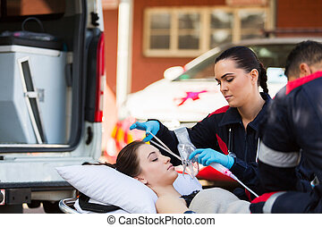 female EMT putting oxygen mask on patient - young female EMT...