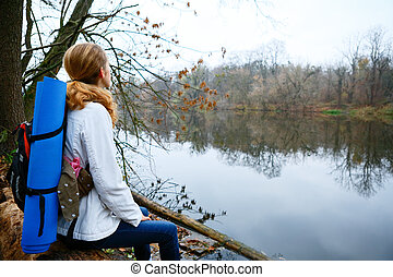 Woman hiker resting on the riverbank. Walking in the weekend