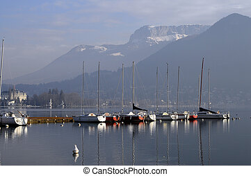 Sailboats on annecy lake with snow on mountain by a quiet...