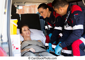 paramedic team talking to patient in ambulance - friendly...