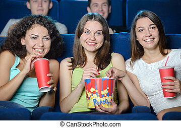 Movie Theater - Exciting movie. Young people eating popcorn...