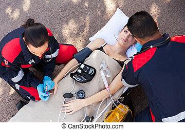 above view of paramedic examining patient - above view of...