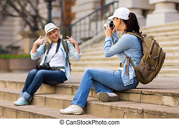 young tourist photographing her friend in the city