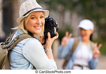 young tourist taking photo of her friend - happy young...