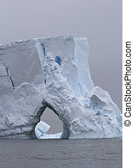 Iceberg with large through entrance on a cloudy day at the coast