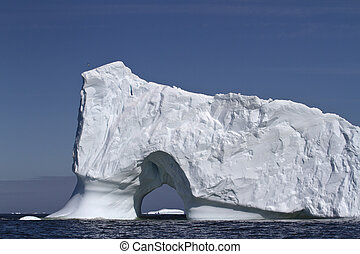 Iceberg with large through the entrance to the ocean off the coa
