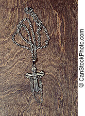 silver cross necklace on wood