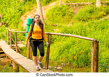 young beautiful tourist in a hike in the woods