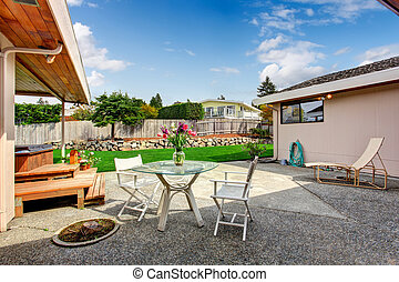 House exterior. Backyard deck with glass top table and chairs