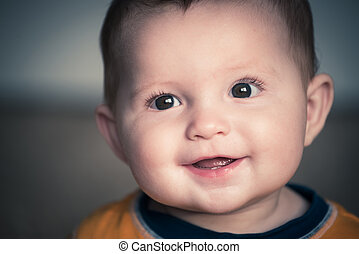 Close up portrait of cute happy baby smiling in vintage filtered
