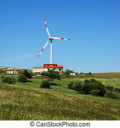 Wind turbine and modern house - Solitary wind turbine behind...