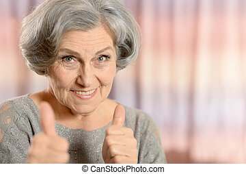 Happy elderly woman showing thumbs up isolated on color...