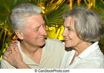 Nice old people on palm leaves background