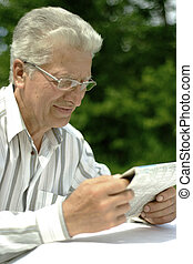 older man reading newspaper - Attractive cute older man...