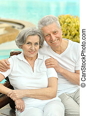 Old loving couple - Senior couple standing by pool at the...