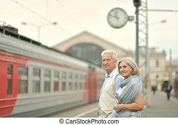 Couple at train station - Mature vital elderly couple at the...