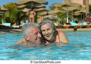 Elderly couple in pool - Elderly couple swimming in pool at...
