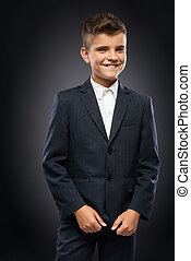 boy in a black suit jacket corrects - cheerful boy in a...