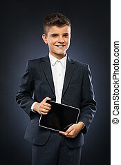boy in black suit holding a tablet - boy in a black suit...