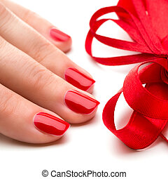 Woman hands with manicure red nails closeup and ribbon. Skin...
