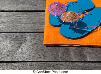 Beach slippers, towel on wood background Concept of leisure...