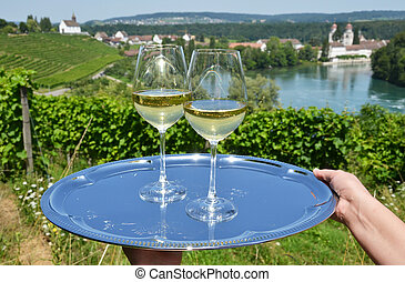 Pair of wineglasses against Rhine river and vineyards in Rheinau