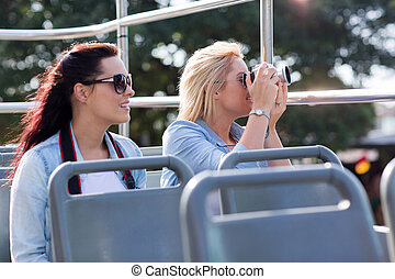 tourists taking pictures from an open top bus while touring...