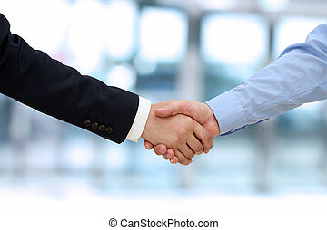 Close-up image of a firm handshake between two colleagues in...