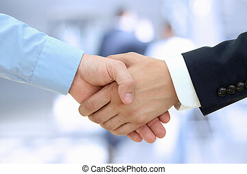 Close-up image of a firm handshake between two colleagues on...