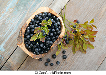Fresh blueberry in wooden bowl on wooden background