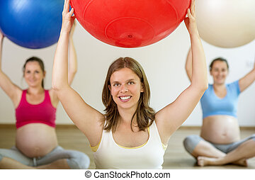 Pregnant women exercising - Young pregnant women doing...