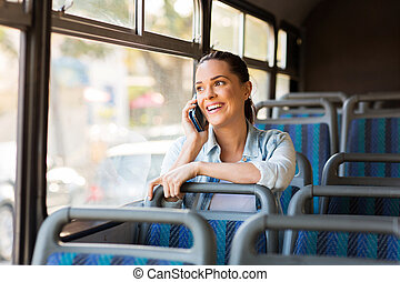 beautiful female commuter talking on cell phone while taking...