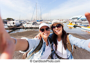 two travellers taking selfie by the harbor - two happy...