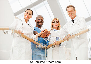 Team of medical experts. Low angle view of four happy...