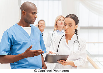 Consulting on the go. Group of confident doctors moving...