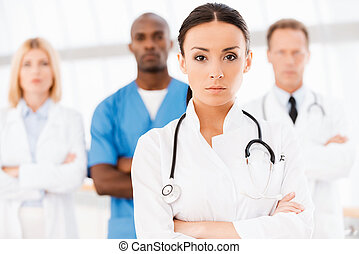 Confident doctor leading her team. Beautiful female doctor...