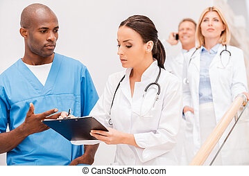 Doctors consulting. Group of confident doctors moving...
