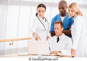 Consulting about proper treatment Group of confident doctors...