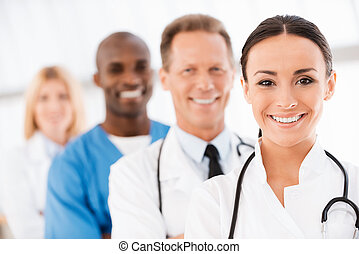 Confident doctors team. Confident female doctor looking at...