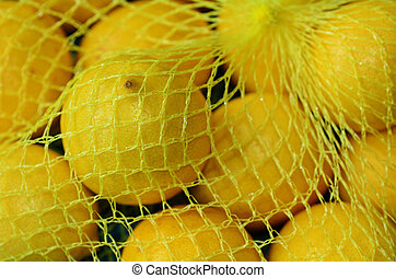 Fresh yellow lemons in plastic netting In Market Food...