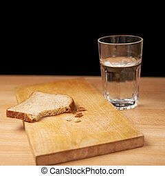 Glass of water and bread composition over the wooden surface