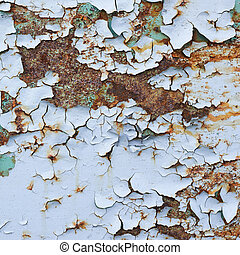 Blue paint flakes falling off the rusty metal surface as a...