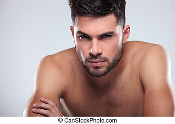 cool undressed man sitting with hands crossed