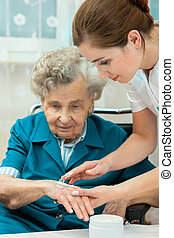 Elderly woman is assisted by nurse at home