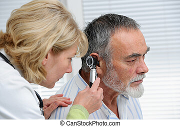Ear examination - ENT physician looking into patients ear...