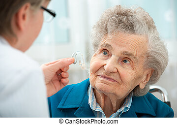 Hearing Aid - Deaf senior woman during a hearing test