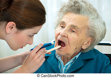 Medical exam - Doctor examines elderly woman for sore throat